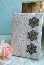 Блокнот формата А5, 160 страниц, которые состарены при помощи кофе до светло-бежевого цвета. Обложка: белое кружево, бежевый атлас и синтепон в качестве подкладки для мягкости. На ней закладка из белой резинки с пришитыми к ней узорчатыми металлическими цветками. Листы скреплены в двух местах прочной ниткой, на форзацах пространство между обложкой и блоком листов скрыто бежевой атласной лентой. Блокнот сделан с нуля и отлично подходит для подарка невесте на свадьбу.