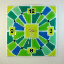 Годинник настінний із кольорового скла, виконаний у техніці фьюзінг. Цифри виконані спеціальним контуром, який запікається при 800 град. Кварцевий механізм додається. Цей годинник стане цікавим акцентом у Вашому інтерєр`і, а яскраві, весняні кольори додадуть Вам гарного настрою.