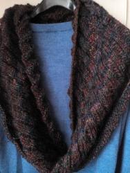 Шарф-снуд, шарф-петля - необходимый и очень удобный аксессуар в холодные зимние дни. Замечательно подходит к куртке, пальто или дубленке. Шарф-снуд связан из мягкой полушерстяной пряжи темно-серого цвета с вплетением зеленых, сливовых, бордовых, рыжих нитей. Длина шарфа позволяет обернуть его вокруг шеи в два оборота и надежно защитить голову и горло от холода и ветра. Шарф связан очень интересной спиральной (эстонской) резинкой. Размер 32*130.