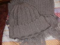 Шапка и шарф связаны спицами из акрила с добавлением металлика. Длина шарфа 2 м, а ширина 26,5 см. Шапка связана в 2 нити, а шарф - ажурным узором.