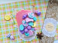 МАТЕРІАЛИ: Декор кружки виконаний з полімерної глини Cernit у ніжних рожевих, фіолетових та бірюзових кольорах у вигляді солодощів    РОЗМІР: Кружка прозора об'ємом 250 мл. та висотою 11 см.