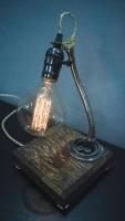 """На замовлення. Термін виготовлення: 5-7 робочих днів.  Настільна лампа """"Pride&Joy"""", виготовлена з авто-деталей і натуральної сосни, з лампою Едісона. Ручна робота з індивідуальним дизайном. Встановлено димер для регулювання яскравості світла на будь-який смак.  особливості: - З унікальних автодеталей і натурального дерева. - Встановлено димер; - Довжина шнура - 150 см.; - Стандартний патрон; - Лампа Едісона входить в комплект;  Основа: 15 cm x 15 cm x 5 cm Висота: 35 cm Вага: 2 kg  Дану модель можна виготовити під замовлення в необхідній кількості. Авто-деталі і шия можуть трохи відрізнятися від заявлених на фото."""