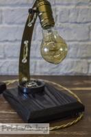 """На замовлення. Термін виготовлення: 5-7 робочих днів.  Настільна лампа """"Pride & Joy"""", виготовлена з авто-деталей, метала і натурального дерева, з лампою Едісона. Ручна робота з індивідуальним дизайном. Встановлено димер для регулювання яскравості світла на будь-який смак.  особливості: - З унікальних автодеталей і натурального дерева; - Встановлено диммер; - Довжина шнура - 150 см .; - Стандартний патрон; - Лампа Едісона входить в комплект;  Основа: 20 cm x 15 cm x 2,5 cm Висота: 35 cm Вага: 2 kg  Дану модель можна виготовити під замовлення в необхідній кількості. Авто-деталі можуть трохи відрізняться від заявлених на фото."""