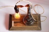 """Под заказ! Настольная лампа """"Pride&Joy"""", изготовлена из авто-деталей, металла и натурального дерева, в стиле """"Industrial"""" с лампой Эдисона. Ручная работа с индивидуальным дизайном. Установлен диммер для регулировки яркости света на любой вкус. Длина — 30 см., ширина — 18 см.  Особенности: - Из уникальных авто-деталей и натурального дерева;  - Все детали очищены и обработаны; - Установлен диммер;  - Длина шнура - 150 см.; - Стандартный патрон;  - Лампа Эдисона входит в комплект; Уход: сухая уборка.  Данную модель можно изготовить под заказ в необходимом количестве."""