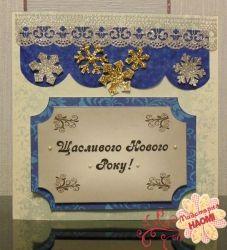 Стильна новорічна листівка декорована виблискуючими об`ємними сніжинками різноманітної форми та срібною блискучою стрічкою.