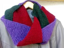 Теплый нарядный шарф-петля – незаменимый предмет осеннего гардероба. Объемный и теплый трехцветный шарф-снуд связан из качественной шерстяной пряжи серого, темно-зеленого и бордового цветов и будет прекрасно гармонировать с яркими красками осени. Снуд выполнен в виде косы из переплетающихся между собой полос, которые создают очень объемный эффект и придают ему дополнительную изюминку. Такой шарф прекрасно подойдет к пальто, куртке или теплому жакету.