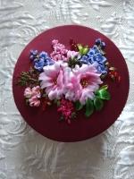 Шкатулка создана при помощи вышивки атласными лентами, бисером и шёлком, в качестве декора использованы кружево и стразовое полотно. Это прекрасный подарок ко дню рождения, на юбилей или в качестве презента.