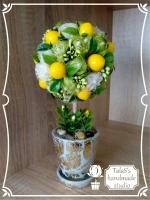 В работе использованы: пенопластовая основа, сизаль 2 цветов, шнур джутовый для декора ствола, незабудка оливковая глянцевая, булавки белые капля, лимон искусственный глянцевый 3*2 см, флористическая зелень: травка с желтыми длинными ягодками, листья рускуса, речная галька. Высота дерева - 24 см, диаметр кроны - 11-12 см. Керамическое кашпо с подставкой (высота - 8 см, диаметр — 7,5 см)
