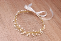 Венок для свадебной прически выполнен из белых и прозрачных бусин разных форм и размеров, бисера. Выполнен на ювелирной проволоке золотого цвета. Длина венка около 50 см, размер регулируется ленточкой Этот венок можно слегка изгибать по форме прически, можно завязать лентой, а можно спрятать кончики в прическу и закрепить невидимками. Очень легкий, милый, романтичный; будет смотреться и с локонами, и с гладкими прядями